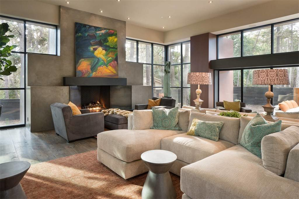 Living Room, End Tables, Sectional, Standard Layout Fireplace, Ottomans, Rug Floor, Dark Hardwood Floor, Chair, Recessed Lighting, and Table Lighting  A Sleek Residence on California's Central Coast Asks $3.9M