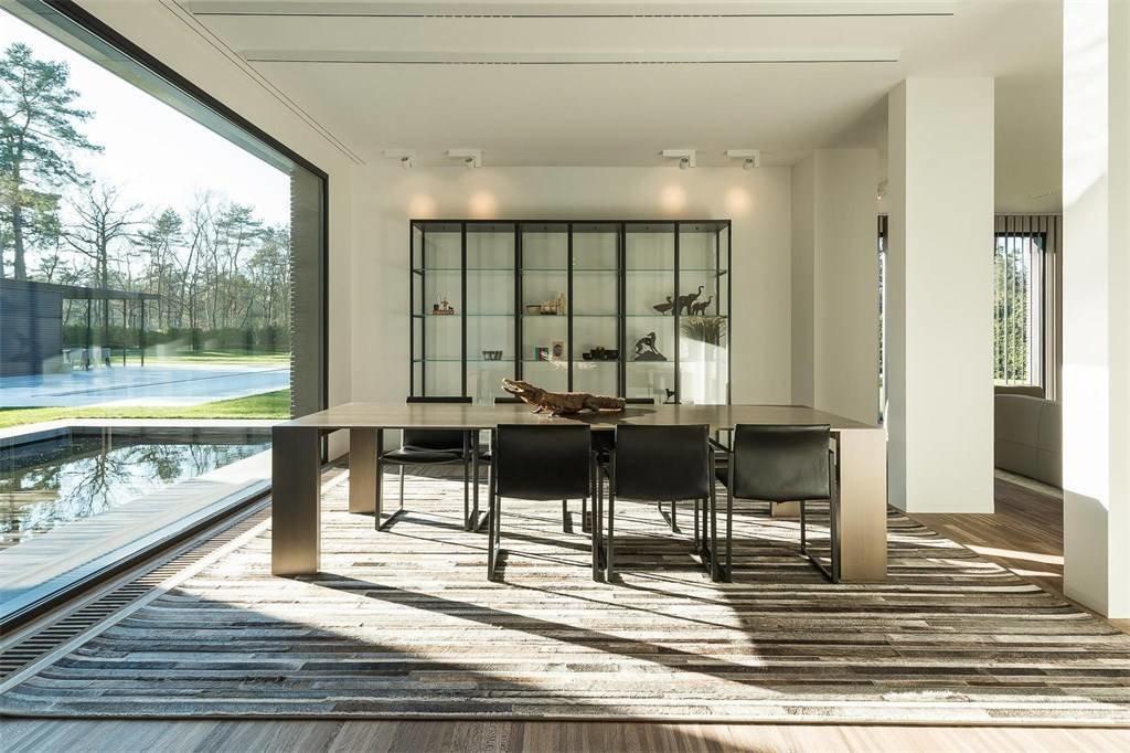 Dining Room, Rug Floor, Wall Lighting, Table, Medium Hardwood Floor, and Chair  Prestigious Modern Villa in Belgium Asks $6.8M