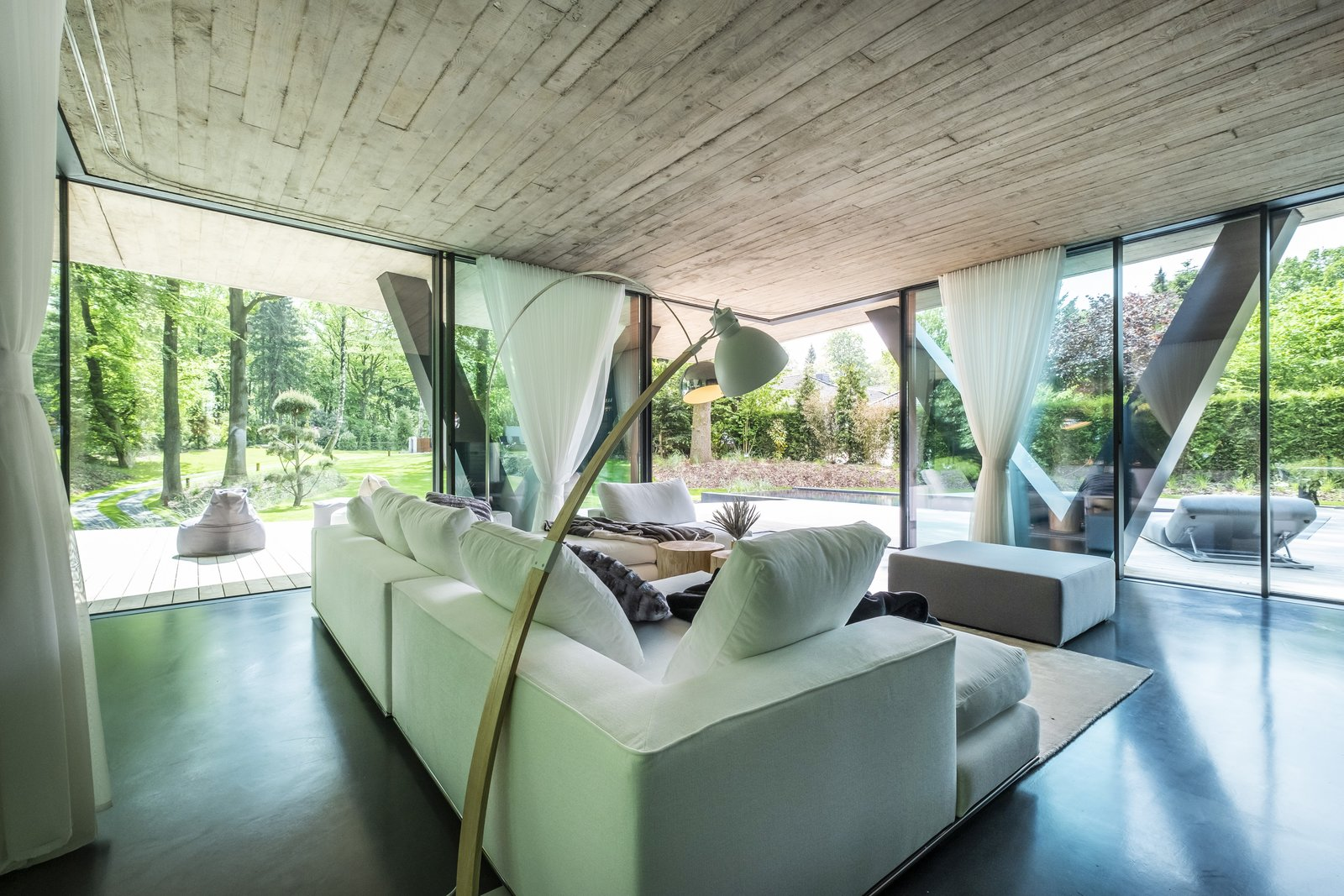 Living Room, Sectional, End Tables, Ottomans, Chair, Floor Lighting, and Concrete Floor  A Sculptural Abode in Germany Asks $3.59M