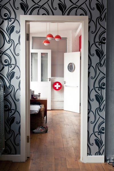 9 Inspirational Examples of Adaptive Reuse - Photo 1 of 9 - View into the bedroom with private terrace from the living room. A simple palette of grays blends with the industrial-chic aesthetic, with splashes of red and gold.