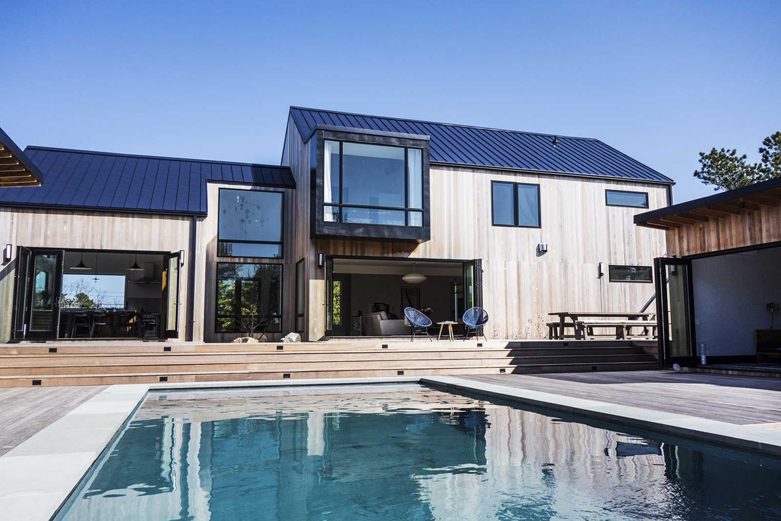 Bi-fold doors connect the main residence to the backyard, which features a large swimming pool, a 200-square-foot pool house, and an outdoor kitchen.  Photo 5 of 11 in Spotted: 10 Modern Homes in the Hamptons