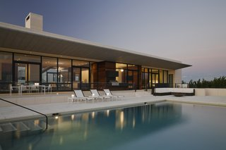 Seen here is the ocean-facing side, with a zinc-clad cantilever shading that covers a sprawling outdoor patio.