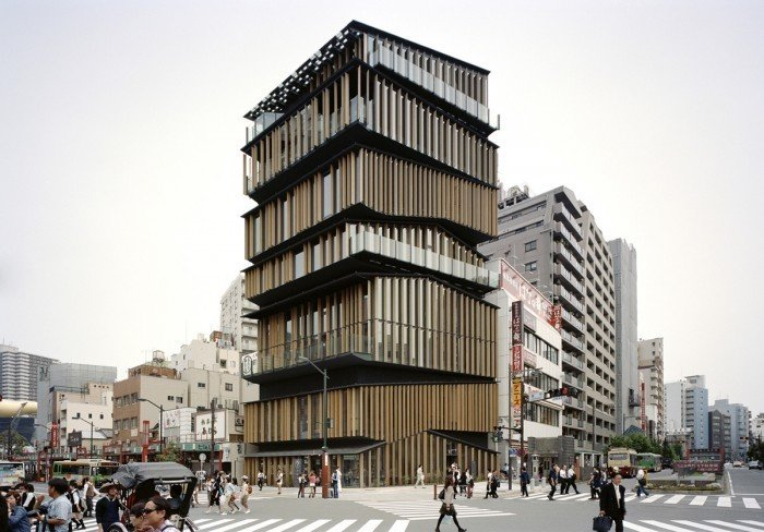 """Resembling a stack of smaller structures with asymmetrical roofs--extending the liveliness of the neighborhood vertically-- the Asakusa Culture Tourist Information Center is located near the outer gate to ancient Buddhist temple Sensō-ji, which was constructed in the sixth century and is the oldest of its kind in the city. The center needed to accommodate multiple purposes : a tourist information center, a conference room, a multi-purpose hall and an exhibition space.    The center extends Asakusa's lively neighborhood vertically and piles up roofs that wrap different activities underneath, creating a """"new section"""" which had not existed in conventional layered architecture. Equipments are stored in the diagonally shaped spaces born between the roof and the floor, and by this treatment we could secure large air volume despite its just average height for high-and medium-rise buildings. Furthermore, the roofs not only divide the structure into 7 one-storied houses but also determine the role of each floor. First and second floor has an atrium and in-door stairs, creating a sequence from which you can feel the slope of the two roofs. On 6th floor, taking advantage of the slanted roof, we were able to set up a terraced floor with which the entire room can function as a theater.  Photo 2 of 13 in Architect Spotlight: 12 Works by Japanese Architect Kengo Kuma"""
