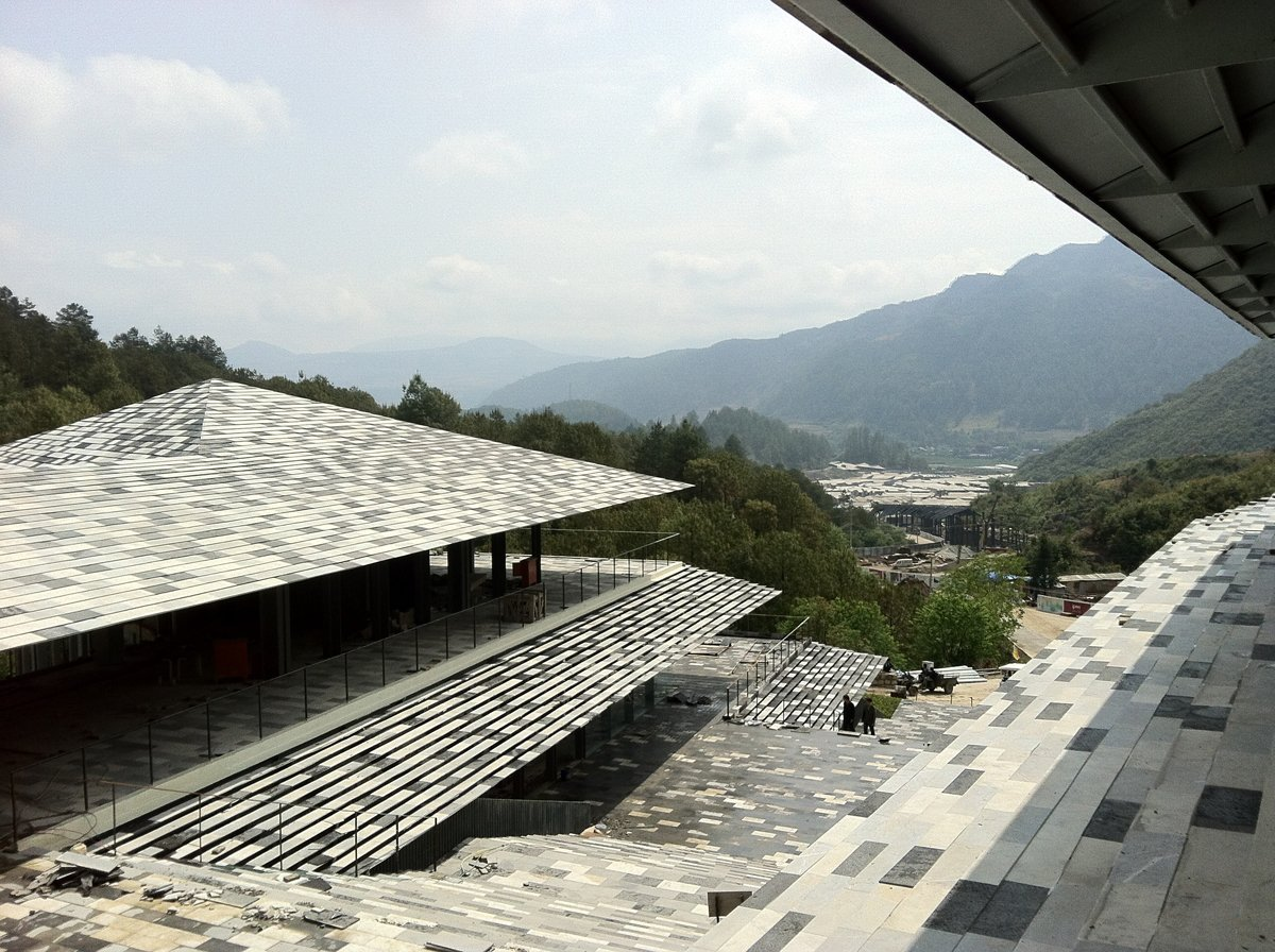 """The spa resort stands in the mountain in Tengchong of Yunnan Province, China. There is a Mountain called Yunfengshan to the west of the site, which is known as a sacred place of Taoism. So we arranged the buildings as if to follow the current of the """"spirit"""" coming down from the mountain. We also utilized different kinds of stones taken from a nearby quarry and put them together like a mosaic. By working on the local stones, we tried to express the power of the earth in the architecture we designed.  Photo 9 of 13 in Architect Spotlight: 12 Works by Japanese Architect Kengo Kuma"""