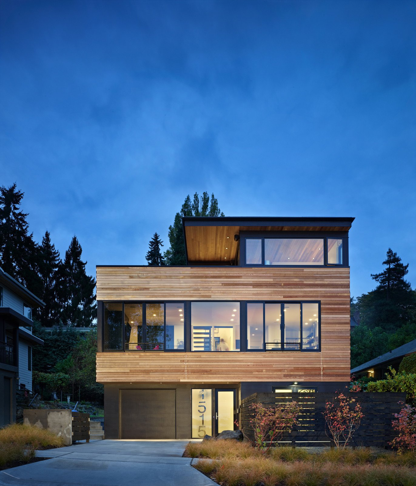 This 2,500 square foot house in Seattle was designed to maximize panoramic views of Lake Washington and the Cascade Mountain Range. The Owners wanted a rugged house that incorporated both industrial and natural materials. They also needed storage space for their 18 bicycles and a Bike Shop--which opens to an enclosed yard--for washing and working on their bikes.  The Main Floor is an open area for Living, Dining and Kitchen with sliding glass doors opening to expansive views of the lake and mountains--in fact, decks and patios at every level allow for a continuous flow from the indoors out.  Photo 4 of 12 in 11 of Our Favorite Pacific Northwest Homes From the Community