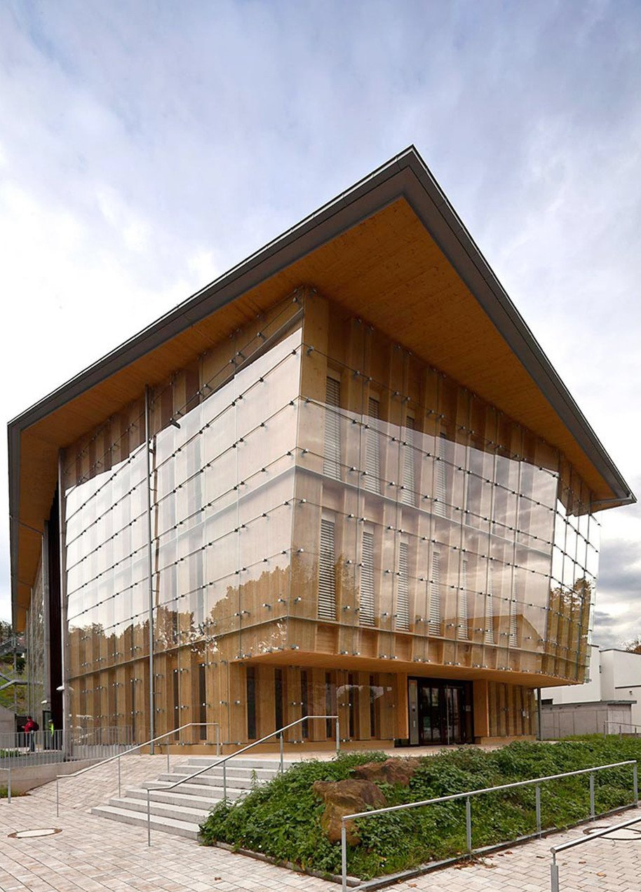 The Farmers' House in Freiburg, Germany, showcases natural wood and glass. The double imbricated glass facade showcases a highly weather proof glass frontage and allows for fascinating light reflections.  Photo 7 of 11 in Glass Takes Center Stage in These 10 See-Through Homes