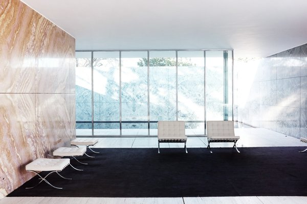 Living Room, Stools, and Chair Designed by Mies van der Rohe as part of the 1929 International Exposition in Barcelona, Spain, The Barcelona Pavilion showcased his iconic Barcelona chair for Knoll and introduced architecture's new modern movement to the world.  Photo 3 of 11 in Less Is More: 10 Buildings by Ludwig Mies van der Rohe