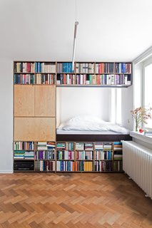 This renovation for a writer in Prague by BY Architects has slotted the bed behind a massive bookshelf in order to meet spatial requirements.