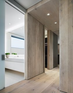 The flooring is comprised of wide-plank Danish oak from Dinesen, which is also featured in select wall panels and used to create the thick, full-height doors to the master bedroom.