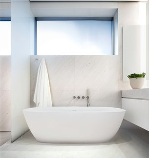 In a building inspired by the environmental elements of light, air, sound, and water, this bathroom in New York embodies captures natural light and shades of white. The Japanese-style soaking tub is a nod to spa chambers, and the finishes are subtle, elegant, and calming.