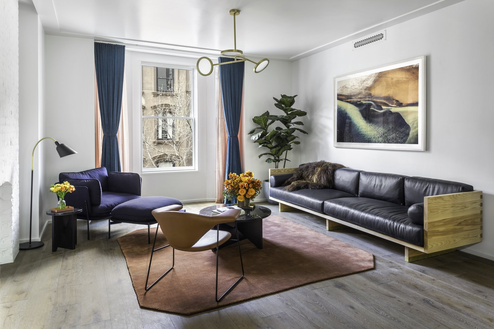 A large custom Matter Made leather sofa defines the living room and creates a cozy space perfect for entertaining.  Photo 3 of 9 in Formerly Home to Superman, The Standish Offers Modernized Beaux-Arts Condos From $1.3 Million