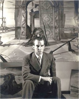 "John Yeon photographed in 1941 at the Julien Levy Gallery in New York. He's seated in front of Eugene Berman's painting, ""Time and the Monuments,"" which Yeon had commissioned."