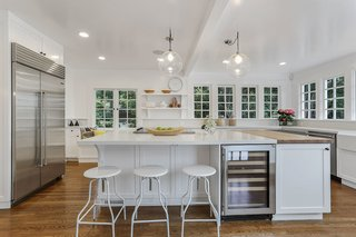The bright and spacious kitchen is full of windows which blend indoors and outdoors. The updated space, which merges historic architecture with modern features, showcases a butler's pantry, breakfast alcove, and deck access for outdoor dining.