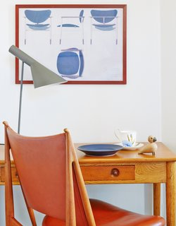 Finn Juhl's Egyptian chair is paired with a Lady Writing Table by Hans J. Wegner. The desk lamp is by Arne Jacobsen.