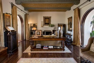 The main house showcases a great room with original gold-leaf ceiling panels and arched mahogany pocket doors, opening the entire home to the gardens and fountains.
