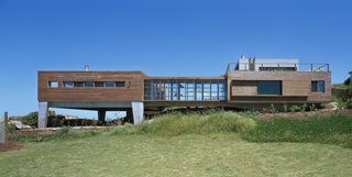 Built from Ipe and exposed concrete, this holiday refuge appears to be emerging from the rocks of its rugged seaside landscape. Located in a fishing village 50 miles north of Punta del Este, on the Atlantic Ocean, the double sloped site of La Roca House is edged by rocks and the remains of the foundation of a pre-existing building which now forms a natural garden of succulents. The home is defined through a sequence of spaces, which consist of two modules of the same height, generating two patios in their voids. The main volume was designed for the social space, and the second for the family's private space—and includes a master bedroom with a stunning panoramic view of the surroundings.