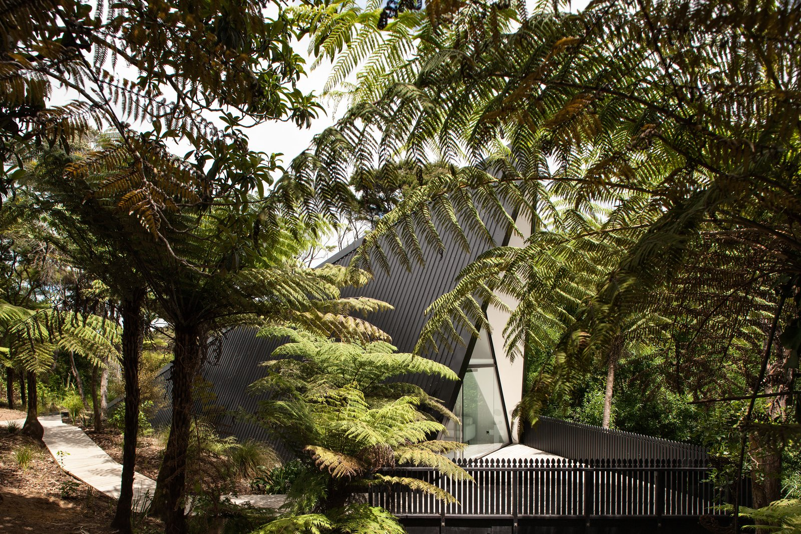 Trees, Shrubs, Front Yard, Small Patio, Porch, Deck, Vertical Fences, Wall, Wood Fences, Wall, Exterior, House Building Type, Metal Siding Material, Metal Roof Material, and Cabin Building Type On Waiheke Island near Auckland, New Zealand, the Tent House sits among wetlands on a patch of undeveloped land. It captures the back-to-basics simplicity of camping, thanks to architect Chris Tate.   Though he originally created the cabin to be a personal retreat/studio, Tate ended up experimenting with the design in order to challenge conventional expectations of what makes an ideal weekend escape. Now available for short-term rental, the one-bedroom, one-bathroom, 753-square-foot home includes a sleeping area on the mezzanine, a fully functional kitchen, an open-plan living area, and a front deck designed to  Photo 1 of 8 in Stay in a Tent-Inspired A-Frame Cabin in the New Zealand Rain Forest