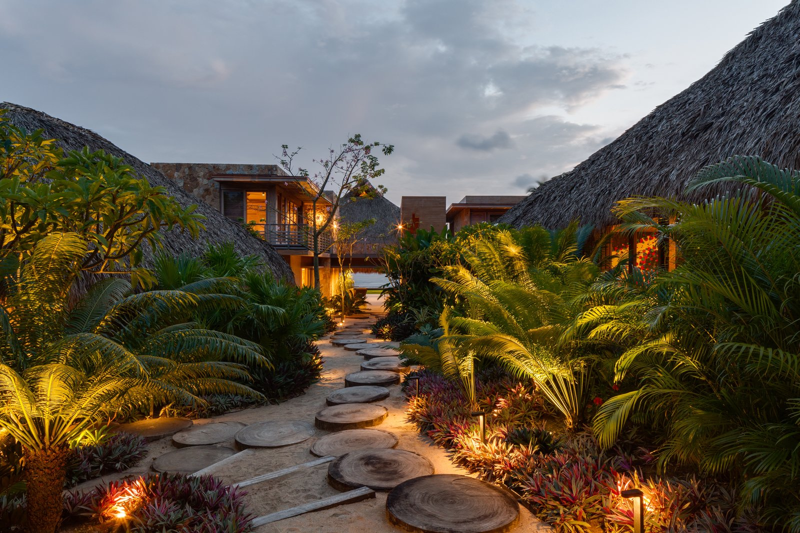 Outdoor, Side Yard, Trees, Walkways, and Landscape Lighting Each of the smaller pavilions is nestled in the landscape of native vegetation and set along a path connected by stepping stones made of cut tree trunks.  Photo 2 of 14 in This Expansive Beachside Home on Mexico's Pacific Coast Puts a Modern Spin on Tradition