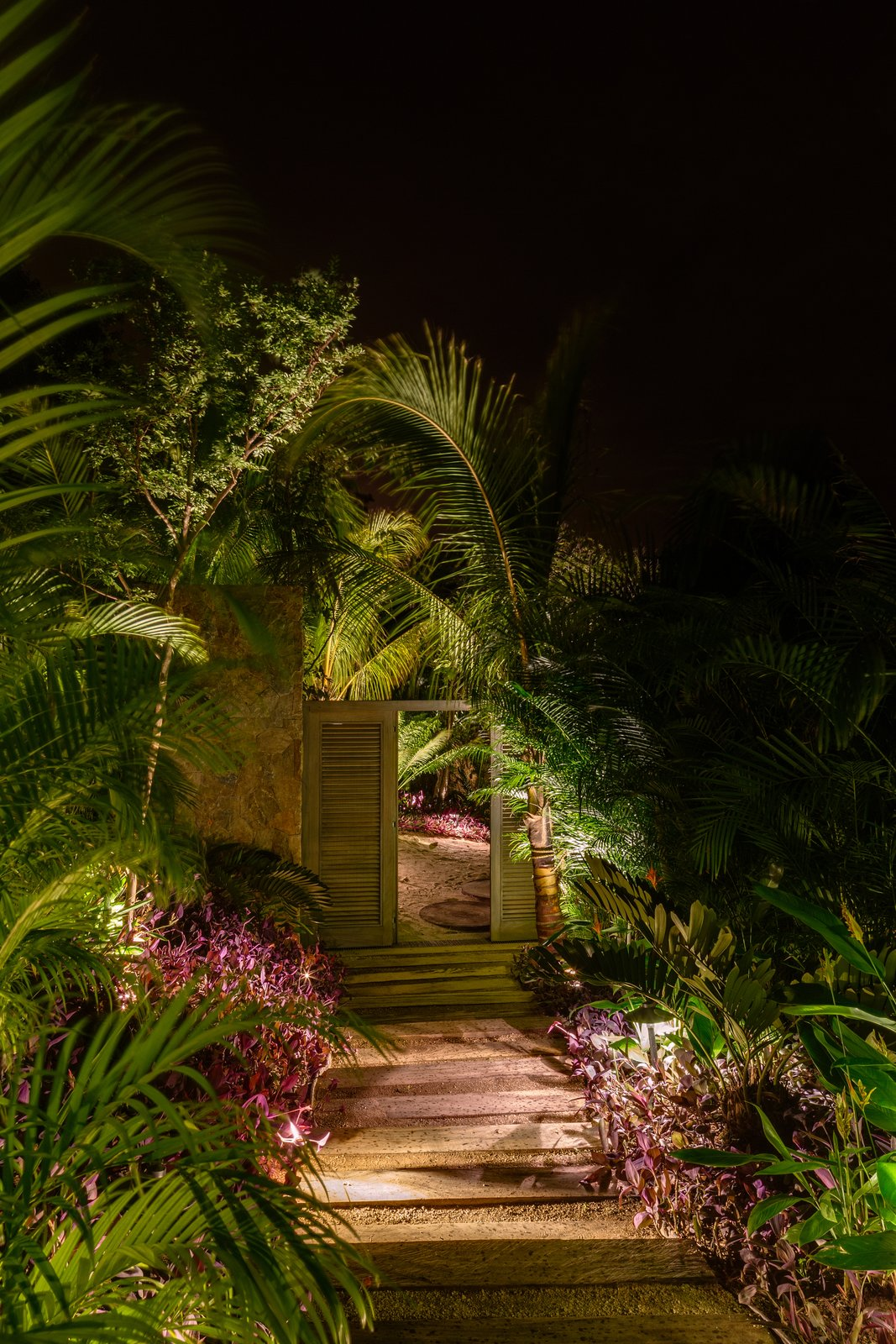 Outdoor, Walkways, Trees, Side Yard, and Landscape Lighting The site is lush with natural local vegetation.  Photo 7 of 14 in This Expansive Beachside Home on Mexico's Pacific Coast Puts a Modern Spin on Tradition