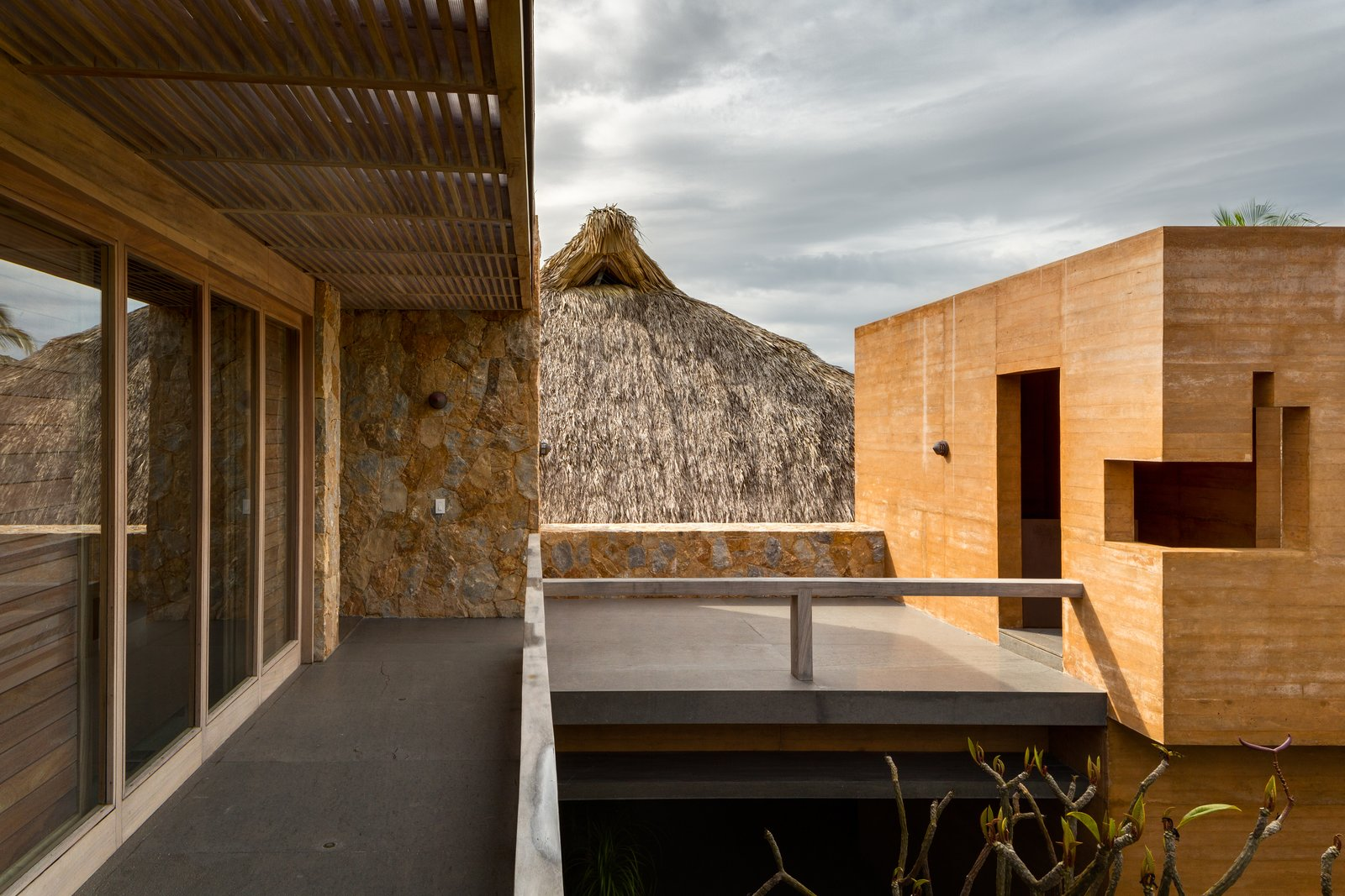 Outdoor, Concrete Patio, Porch, Deck, Small Patio, Porch, Deck, Side Yard, and Wood Fences, Wall The natural materials areputting a contemporary spin on tradition.  Photo 10 of 14 in This Expansive Beachside Home on Mexico's Pacific Coast Puts a Modern Spin on Tradition