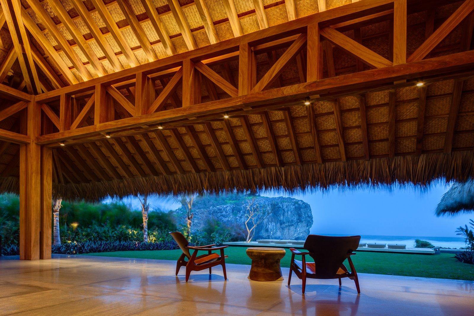 Outdoor, Back Yard, Trees, Grass, Hardscapes, Large Patio, Porch, Deck, and Landscape Lighting A spectacular ocean view in a equally spectacular setting.  Photo 12 of 14 in This Expansive Beachside Home on Mexico's Pacific Coast Puts a Modern Spin on Tradition
