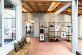 Comey's shop features terra-cotta-colored floors, wood beam ceilings, skylights, and a wraparound wicker bench.