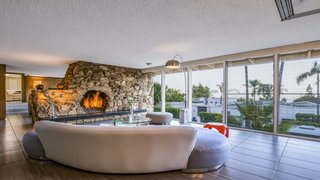 Experience L.A. Like an A-Lister at One of These Modern Short-Term Rentals - Photo 5 of 11 - The large, open floor plan creates a free-flowing connection between the living, dining, and entertaining spaces. A massive natural rock fireplace holds court in the living area.
