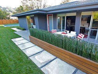 Although L.A. isn't a walking city, this midcentury home is actually walking distance from coffee shops and restaurants. The contemporary interiors of the home feature an open-plan design with sliding doors for privacy. The property also has a private gated yard and a spectacular outdoor space that's complete with a saltwater pool and hot tub.