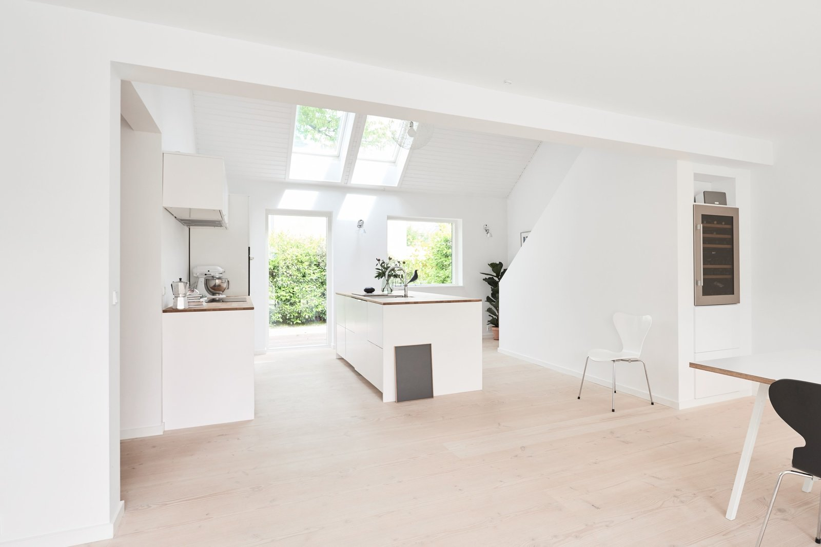 Henning Larsen Architects' design was used in spray painted white with painted metal bands that have been painted the same color and oak counter tops for this bright and airy contemporary home in Charlottenlund, Denmark. Tagged: Kitchen, White Cabinet, Light Hardwood Floor, Wood Counter, Wall Lighting, Refrigerator, Range, Drop In Sink, Range Hood, Pendant Lighting, and Beverage Center.  Photo 6 of 9 in Modern Kitchen Upgrade Ideas From a Danish Design Firm That's Challenging the Kitchen Market