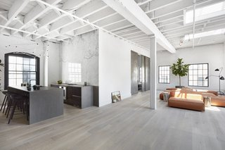 The simple handleless design of the Norm Architects x Reform kitchen is one of the company's bestsellers. Interior designer Alsun Keogh customized the Norm kitchen design for this loft in New York's Soho neighborhood with tombac fronts and concrete countertops.