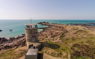 "Set on a cliff top overlooking Corbière lighthouse on Jersey's south-west tip, the Radio Tower covers six floors and boasts a stunning 360-degree view. Built during the Second World War by German Occupying Forces, the Radio Tower is one of Jersey's most iconic sites standing on the south-west tip of Jersey's shoreline. Restored in a German modernist Bauhaus style, with a concrete staircase winding up six floors through the center of the building and leading to a wooden spiral staircase to the top floor. Original features include observation slots on the seaward side and steel doors on the ground floor. <span style=""color: rgb(204, 204, 204); font-size: 13px;"">TripAdvisor Rentals</span>"