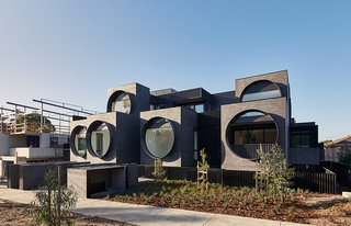 BKK Architects designed this 44-apartment block in a suburb of Melbourne with six porthole windows to provide a strong focal point. The windows span almost the full height of six cubes that face the street and flood the interiors with natural light.