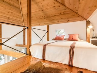 It's an open space with a cathedral ceiling and exposed-cedar beams. There's a queen-sized bed on the main level and another in the loft area.