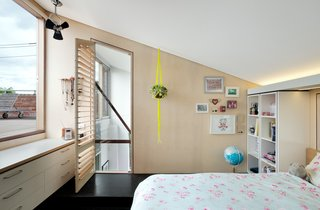 This little bedroom in a plywood pod looks out to the roof-deck and features angled ceilings and strategic lighting that's hidden above a shelving unit.