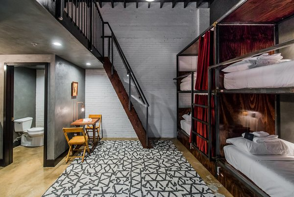 """The bunk beds in the communal """"Loft Room"""" are tucked into handcrafted bunks complete with privacy curtains, a lamp, and plug."""