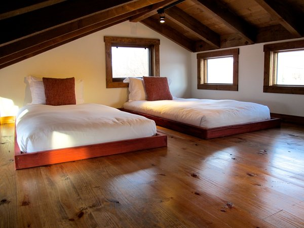 A lofted bedroom with a pair of simple, low beds