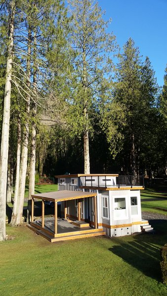 The Flat Roof Caboose design features a loft that can accommodate two beds. Windows give the loft area an open-air feel with an abundance of light. The front of the cabin opens to a private deck. Exteriors are covered with a mix of metal and wood-tone siding for a contemporary finish.