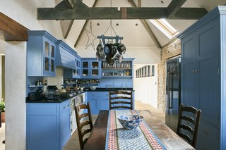 The kitchen is located in the old stone gasworks and features a vaulted ceiling and bespoke, painted cabinets.