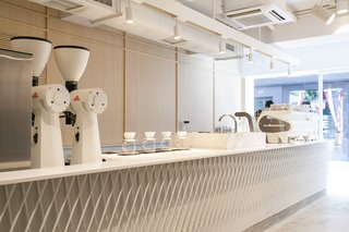 Custom-made by Studio Adjective, the 23-foot-long coffee bar is topped with a white Corian counter.