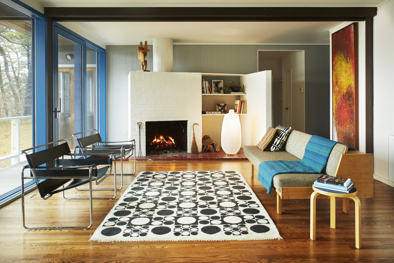 Living Room, Stools, Chair, Sofa, Shelves, Floor Lighting, Medium Hardwood Floor, Rug Floor, Standard Layout Fireplace, and Wood Burning Fireplace  Photo 1 of 9 in Experience Cape Cod Modern by Staying at the Midcentury Weidlinger House