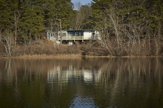 Anchored on concrete piers at the higher end of the slope, the house shoots out over stilts, suspended in midair for a commanding view of Higgins Pond.