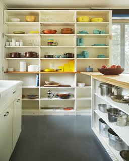 The kitchen's open shelving serves as a colorful display for midcentury-modern cookware.