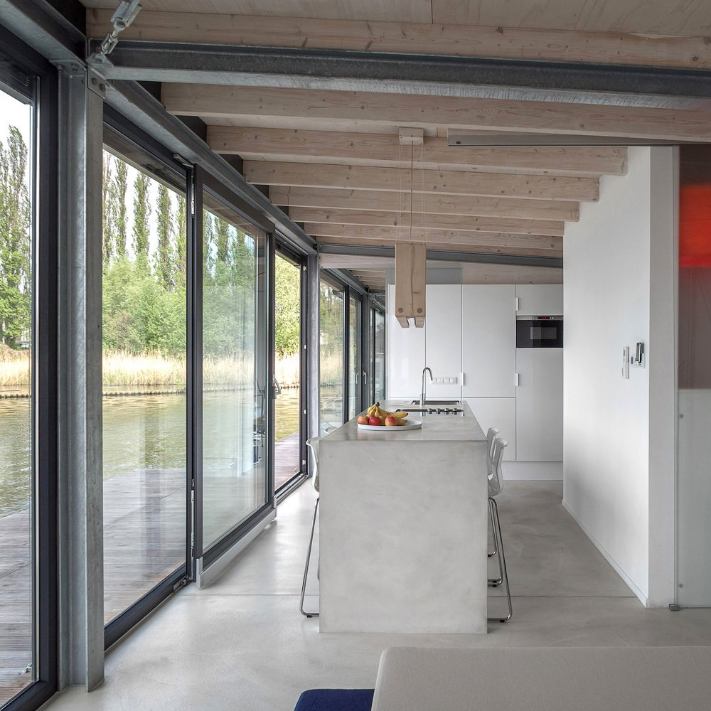Kitchen, Concrete, Concrete, White, Pendant, Wall Oven, and Drop In  Best Kitchen Concrete White Photos from Stay in a Modern Houseboat in Berlin With Floor-to-Ceiling Windows