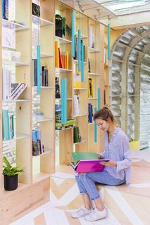 "The ""library"" is designed with a shelving system that allows light to enter, opening up the narrow living space."