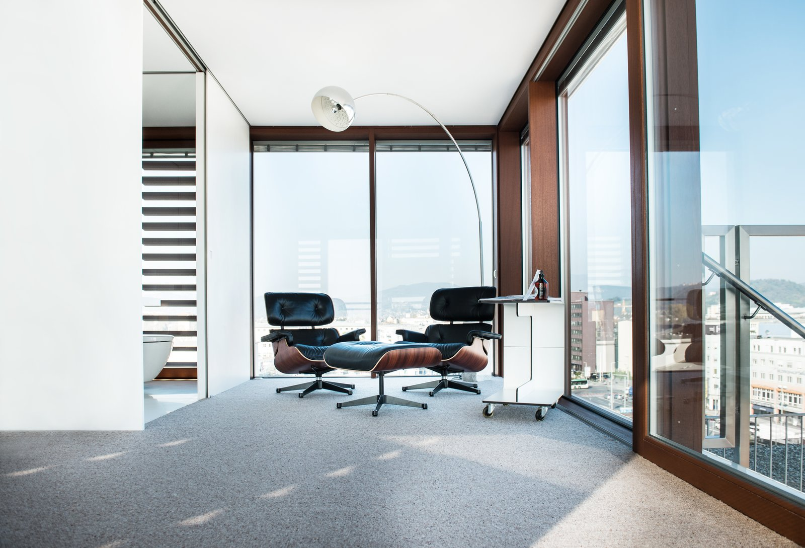 Living Room, Chair, Ottomans, Floor Lighting, and Carpet Floor  Photo 6 of 8 in Stay in a Prefab Cube Placed Atop a Midcentury Hotel in Austria