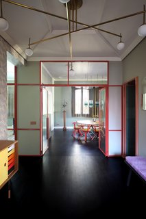 "The apartment's entrance is lined with ""Vanessa"" wallpaper by Mini Moderns. The space features a Finn Juhl sideboard in teak, a chandelier in brass and glass by Commute Design, an Obei Obei mirror by Atipico, and vintage 1950s ceramics from Arts & Crafts Gallery in Venice. There's also a Bench One by Another Country that's been covered in Pillar fabric by Kvadrat."