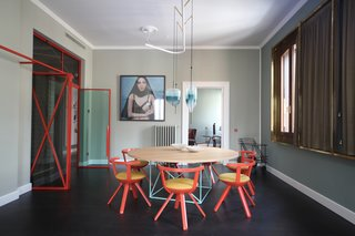 The eclectic dining room houses a LC15 table by Le Corbusier for Cassina, Rival Chairs by Konstantin Grcic for Artek with Kvadrat fabric, a bar cart by Rossana Orlandi, and Flow pendant lights by Wonder Glass. The windows are covered with curtain fabric from Black Edition, along with brass frames by Marcante-Testa that were built by Om Project.