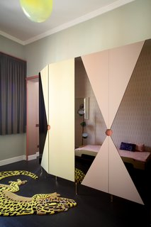This funky bedroom features a Salamandrian carpet by JIWONXKIM, a blow-suspended lamp by &Tradition, a Tam Tam floor lamp by Marset, and a wardrobe made of lacquered-MDF and pink mirrors. It partially hides a stacking bed by Muller Mobelweskstatten.