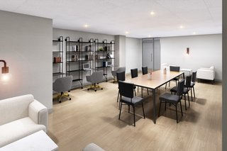 Individual workstations and a conference table are included in the in-house co-working space.