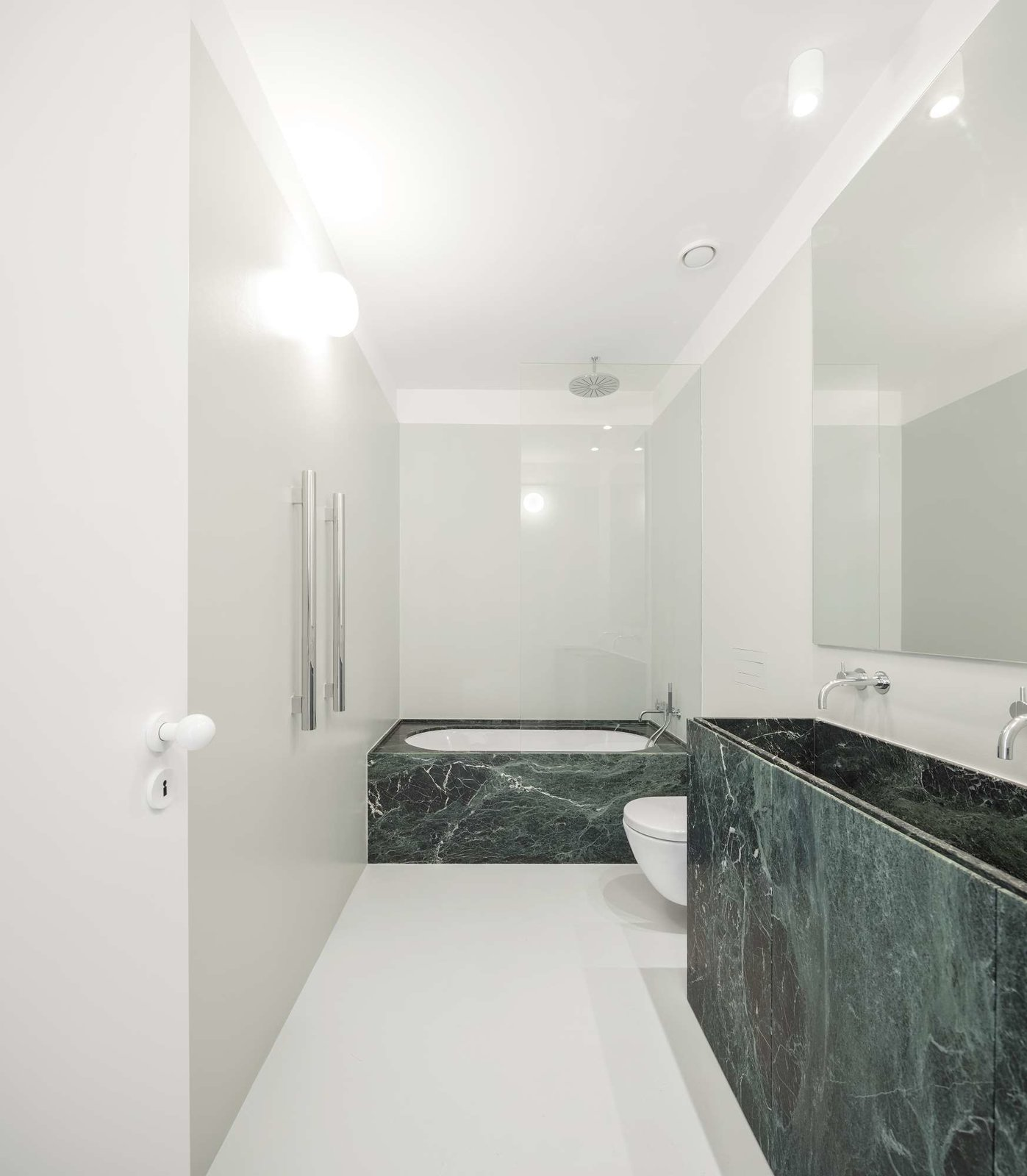 Bath Room, Undermount Sink, Undermount Tub, Stone Counter, Ceiling Lighting, Wall Lighting, One Piece Toilet, Open Shower, and Marble Counter  Photo 8 of 16 in A Luminous Renovation in Portugal Creates a Bright and Airy Apartment
